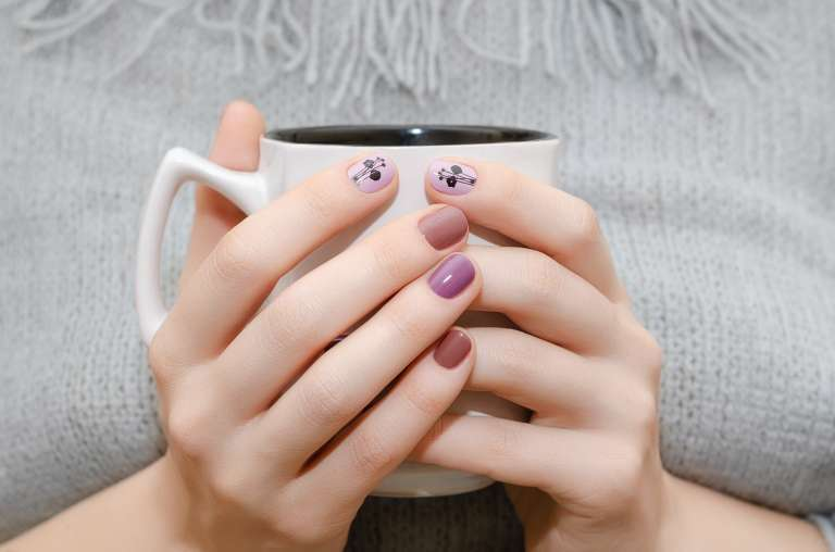 Female Hands With Purple Nail Design Holding White Cup